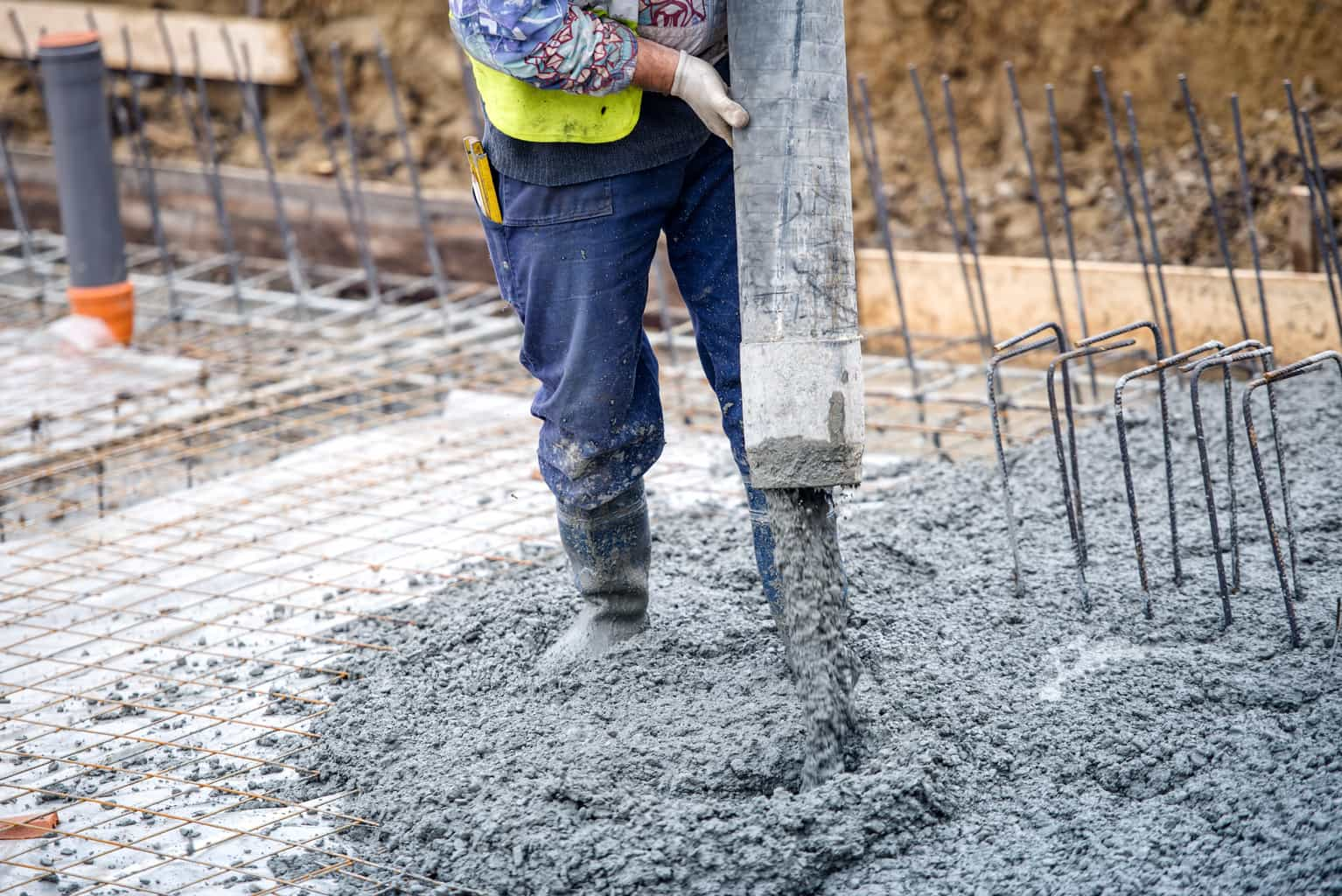 building construction worker pouring cement or concrete with pump tube