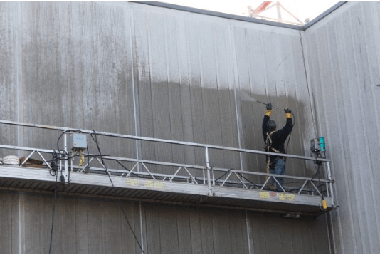 Worker spraying MCI to building